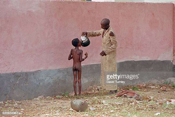A Somali man pours water into the mouth of a starving young boy at the refugee camp in Baidoa