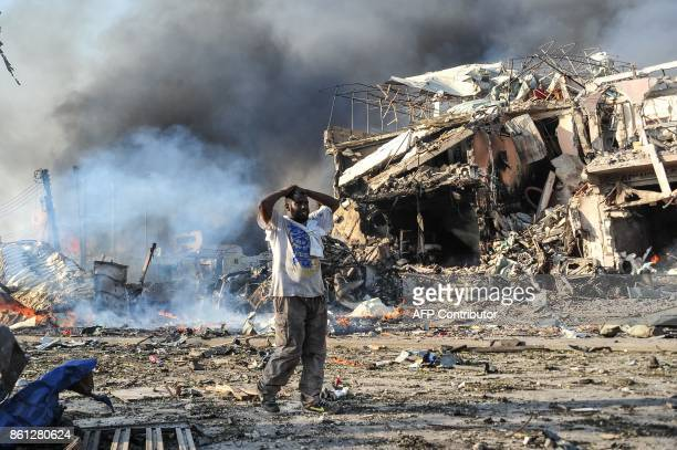 Somali man reacts next to a dead body on the site where a car bomb exploded at the center of Mogadishu on October 14 2017 More than 20 people were...