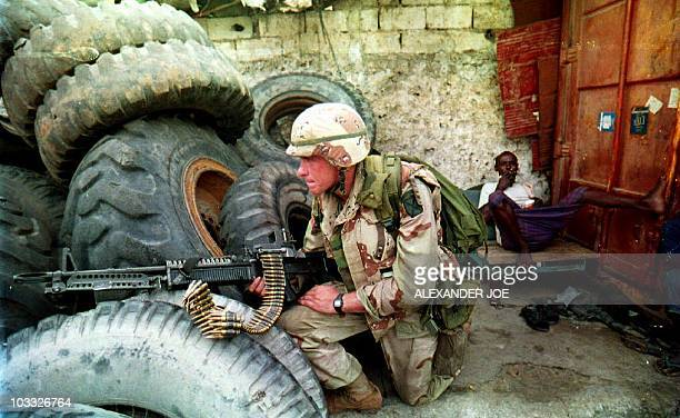 A Somali man sits back and smokes 31 August 1993 as a US soldier guards the front gate of a garage that was being searched for arms They found a...