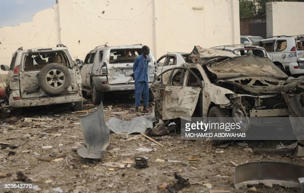 A Somali man stands in the middle of the wreckages of cars as he looks at the scene of a suicide car explosion in front of Doorbin hotel in Mogadishu...