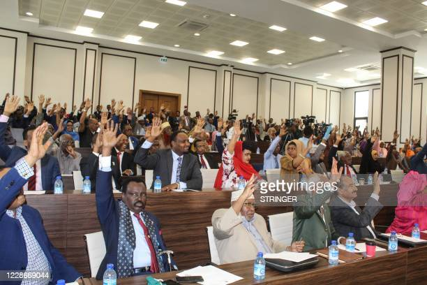 Somali members of Parliament raise their hands to approve the new Somali Prime Minister Mohamed Hussein Roble a Swedishtrained civil engineer in...