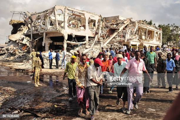 Somali men carry the body of a victim who died in the explosion of a truck bomb in the centre of Mogadishu on October 15 2017 A truck bomb exploded...