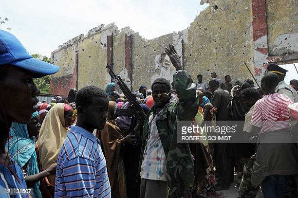 A Somali militiaman shouts at a crowd as he tries to keep a crowd under control outside a food aid distribution center in Somalia's capital Mogadishu...