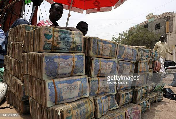 Somali money changer talks on phone on March 8 2012 next to piles of banknotes on the dusty street of Hargeisa in Somaliland the northern breakaway...