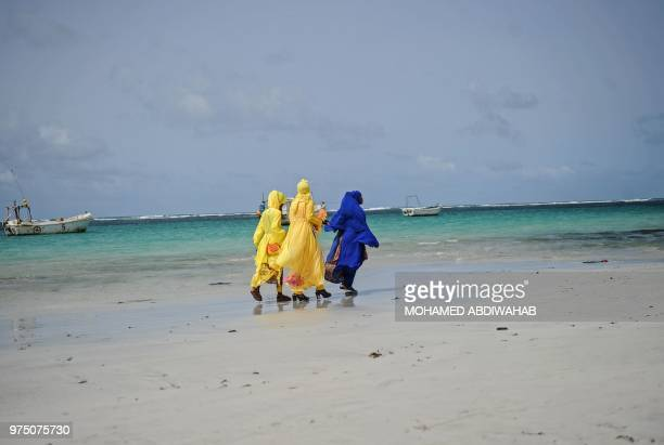 Somali Muslim women walk along Lindo beach on June 15 2018 during the Eid alFitr celebration which marks the end of the holy month of Ramadan at...