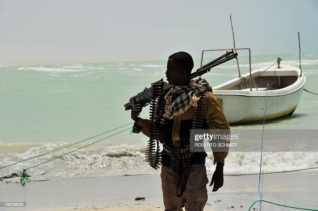 Somali, part armed militia, part pirate, carries his high-caliber weapon on a beach in the central Somali town of Hobyo on August 20, 2010. Hobyo has no schools, no clinics and bad drinking water sources. Fighting a losing battle against the sand that has already completely covered the old Italian port, Hobyo's scattering of rundown houses and shacks looks anything but the nerve centre of an activity threatening global shipping.