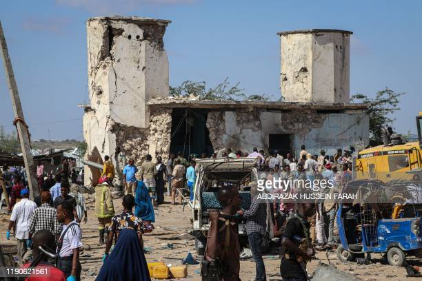 Somali people gather at a car bombing attack site in Mogadishu on December 28 2019 A massive car bomb exploded in a busy area of Mogadishu on...