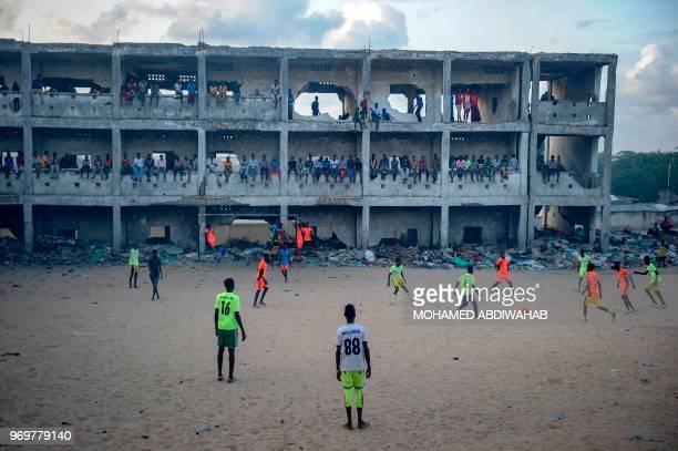 TOPSHOT Somali people play football in the smoky air due to burning litters at the destroyed and abandoned secondary school since 1991 in Mogadishu...