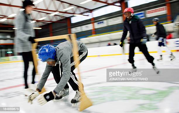 Somali players skate under a barrier as they take part in the Somali national Bandy team's training session on September 24 2013 in the city of...
