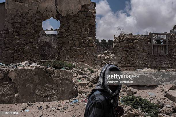 Somali police man walks by a destroyed building on October 11 2016 in Barawe Somalia Barawe was a stronghold for the AlShabaab militant group in...