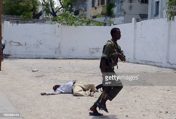 A Somali police officer runs for cover past a dead body on