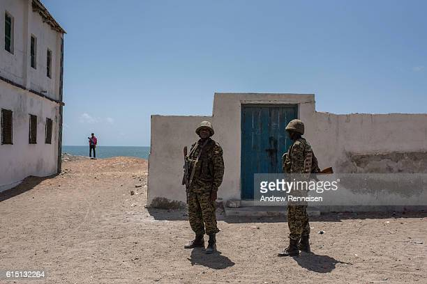 Somali police officers and Ugandan soldiers deployed with the African Union Mission in Somalia stand guard outside a school during a visit by...