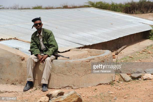 Somali policeman sits beside a traditional cistern for harvesting rainwater called a berkad made by the Irish charity ConcernWorldwide as the Horn of...