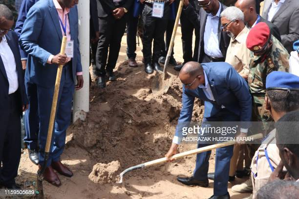 Somali Prime Minister Hassan Ali Khayre uses a a shovel to dig a grave on August 4 2019 in Mogadishu during the funeral ceremony of late Mogadishu's...