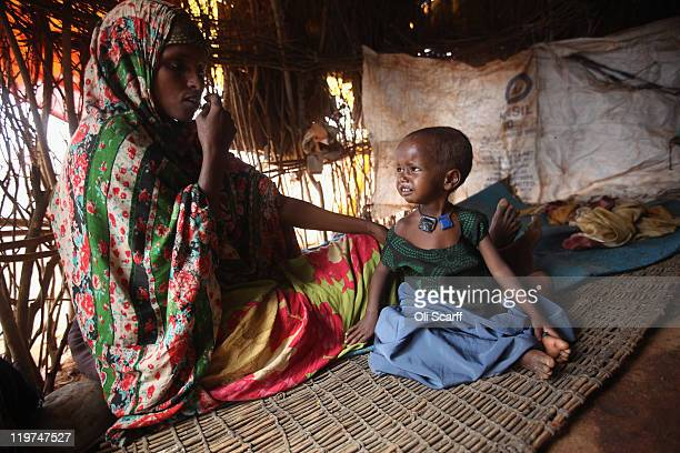 Somali refugee Arfon Mohummd sits with her ill daughter Farhiya Abdi in their makeshift hut on the edge of the Hagadera refugee camp which makes up...