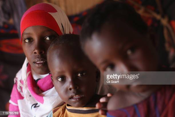 Somali refugee children sit in their makeshift hut on the edge of the Hagadera refugee camp which makes up part of the giant Dadaab refugee...