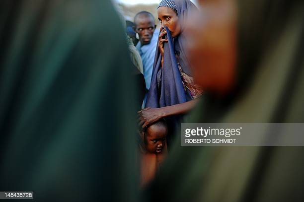 A Somali refugee patiently waits in line with her daughter in the early morning outside a food distribution point in Dadaab refugee camp in...