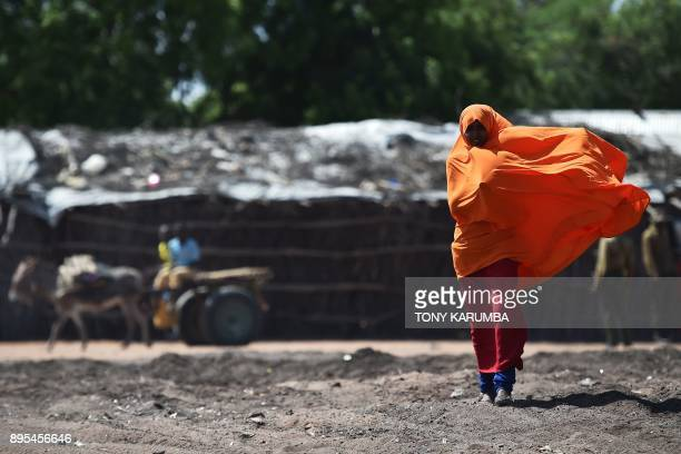 Somali refugee walks along a dirt road in nothern Kenya's Dadaab refugee camp near a rehabilitation centre for refugee womensurvivors of Genderbased...