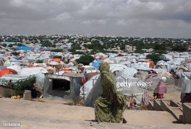 A Somali refugee walks in front of a camp for internally displaced people near the Parliament in Mogadishu on December 4 2012 The humanitarian crisis...