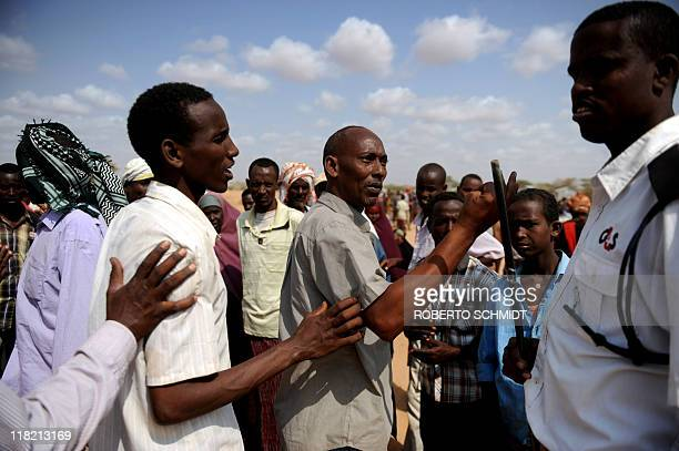 Somali refugees complaint to a security guard about waiting in disorganized lines for hours outside a registration and food distribution point at the...