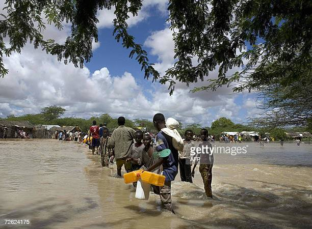 Somali refugees displaced by floods cross a swollen river in Dadaab, Garissa district in Kenya's arid northeastern province 22, November 2006. Barely...