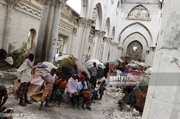 Somali refugees sit among makeshift shelters on August 12 2011 in what used to be the Roman Catholic cathedral in Somalia's capital Mogadishu in the...