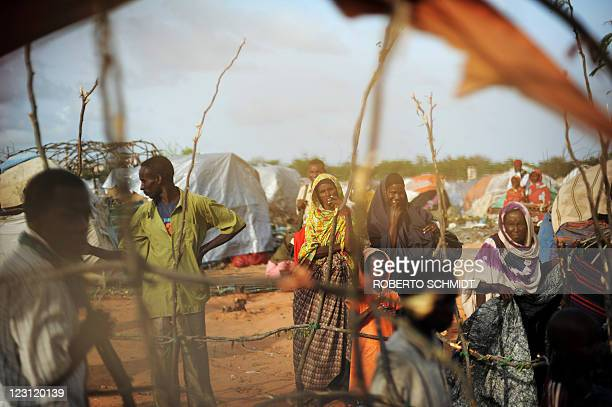 Somali refugees stand near makeshift shelters in a camp for Internally Displace Persons in Mogadishu on August 12 2011 The UN warned Today that a...