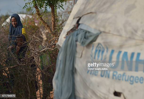 Somali rRefugees peer over a thisle fence in a neighbouring compound at Hagadera sector of the Dadaab refugee camp north of the Kenyan capital...