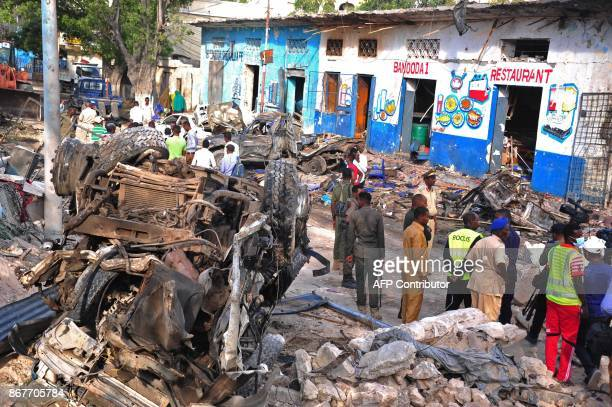 Somali security forces and civilians walk among damages at the scene of a blast on October 29 a day after two car bombs exploded in Mogadishu...