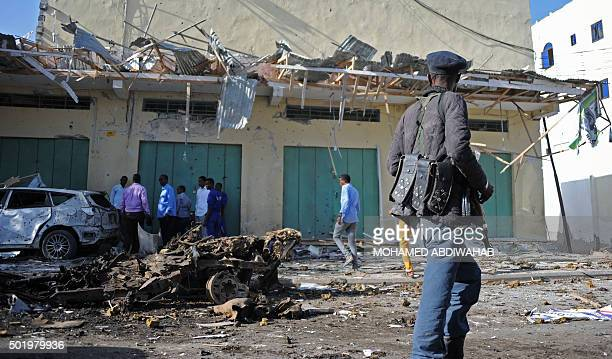 Somali security forces inspect the site of a bomb blast near Makka alMukarama Road in the Somali capital Mogadishu on December 19 2015 Several people...
