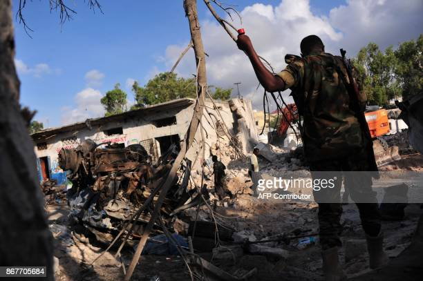 Somali security forces walk among damages at the scene of a blast on October 29 a day after two car bombs exploded in Mogadishu Somalia's security...