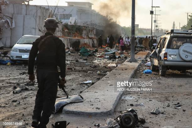A Somali security officer looks towards the scene of twin car bombs that exploded within moments of each other in the Somali capital Mogadishu on...