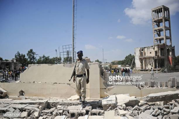 A Somali security officer stands at the scene of a car bombing attack in Mogadishu Somalia on December 222018 Seven people were killed in a double...