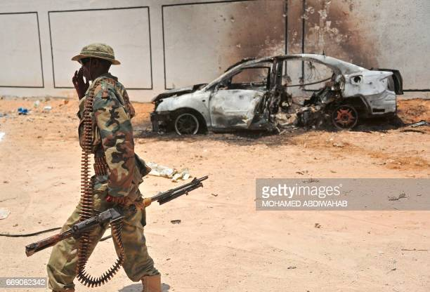 A Somali soldier patrols next to the burntout wreckage of a car that was used by suspected alshabab fighters on April 16 2017 Somali security forces...