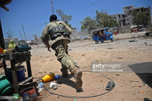 Somali soldier runs for cover at the scene of two explosions set off near the ministries of public works and labour in Mogadishu on March 23 2019 At...