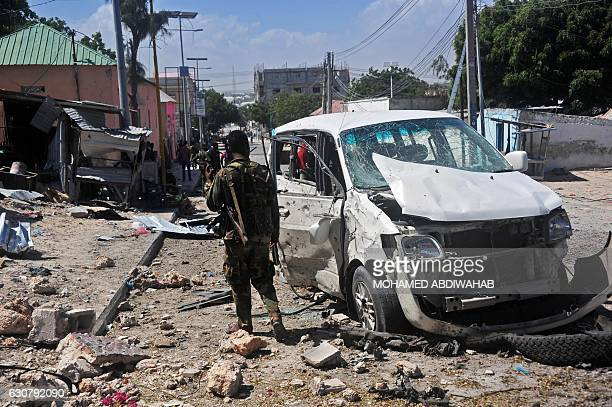 A Somali soldier stands at the scene of a car bomb attack near the Peace Hotel of the capital Mogadishu on January 2 2017 Twin suicide car bombs...