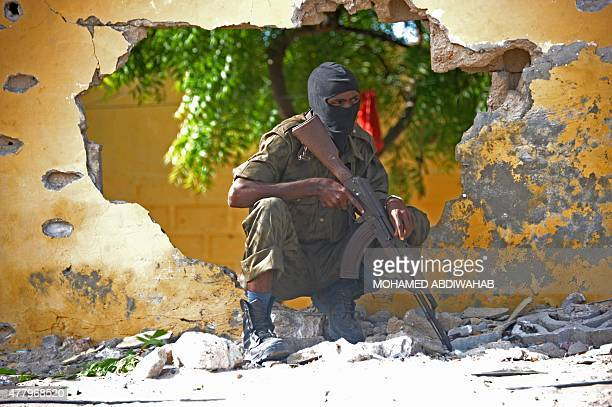 Somali soldier stands guard next to the site where Al Shebab militants carried out a suicide attack against a military intelligence base in Mogadishu...