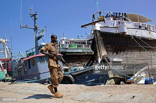 A Somali soldier walks past foreign ships in Bosaso harbor in Puntland on November 18 2013 After increased security in Somalia's Puntland region...