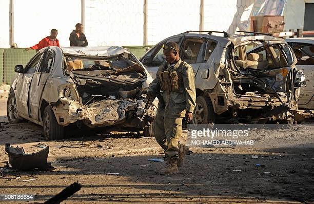 Somali soldier walks past wrecked cars in front of the Lido seafood restaurant on January 22 2016 following an overnight attack on the beachfront...