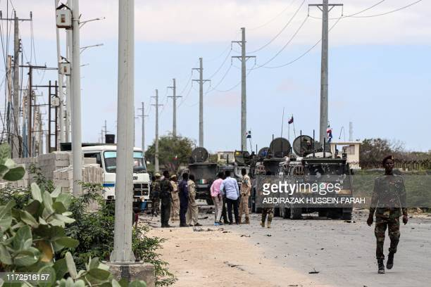 Somali soldiers gather at the site of a suicide car bomb explosion which targeted a European Union vehicle convoy in Mogadishu, Somalia, on September...