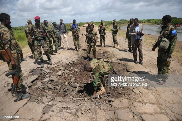 Somali soldiers look at a blast mark of car bomb attack at a check point near Sanguuni military base, where an American special operations soldier...