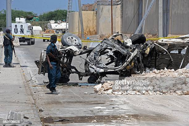 Somali soldiers pass near the wreckage of a car bomb outside the UN's office in Mogadishu on July 26, 2016. At least 13 people were killed on July 26...