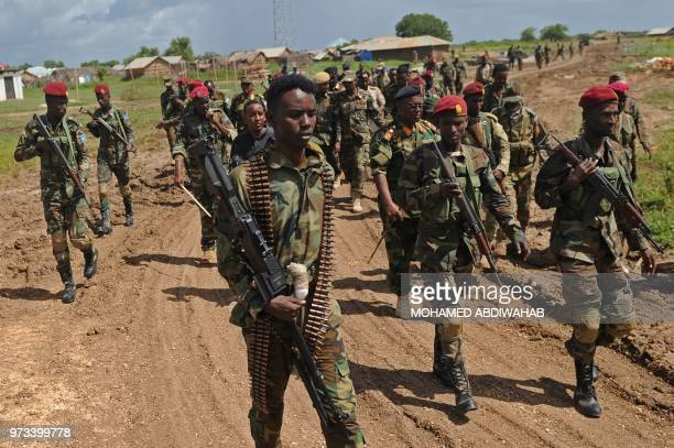 Somali soldiers walk at Sanguuni military base where an American special operations soldier was killed by a mortar attack on June 8 about 450 km...