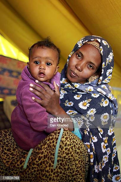 Somali woman and her child sit in their tent at a United Nations displacement camp on March 13 2011 in Ras Jdir Tunisia As fighting continues in and...