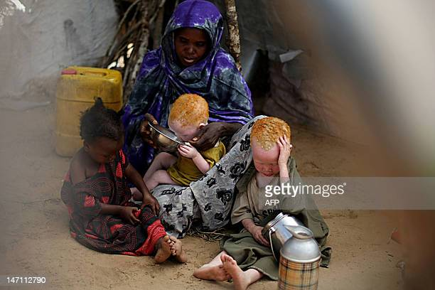 Somali woman Bangi Iftin who fled the recent fighting in Mogadishu shares breakfast with three of her ten children at an internally displaced camp on...