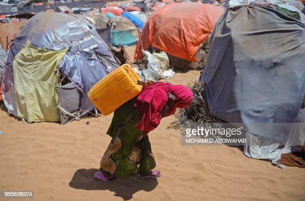 A Somali woman carries a jerrycan filled with water from a well at the Tawakal IDP camp on the outskirts of Mogadishu Somalia on March 2018 World...
