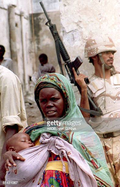 Somali woman carrying her child walks past a United Arab Emirates soldier 08 September 1993 after she obtained some corn during a food distribution...