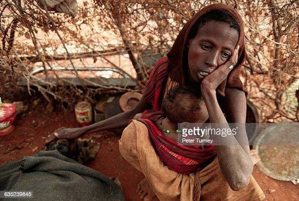 A Somali woman grieves for her dying husband while breast feeding her baby All three are starving from the famine that struck Somalia in 1992