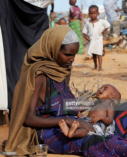 A Somali woman holds her child as she sits in front of a makeshift tent she now calls home at a camp for Internally Displace Persons in Mogadishu on...