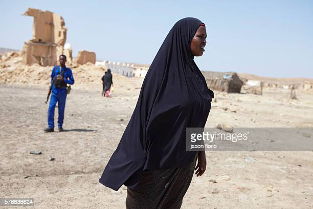 Somali woman in a black Muslim hijab in the village of Elayo near Bosaso, Somalia witha member of the Puntland Maritime Police Force in the...